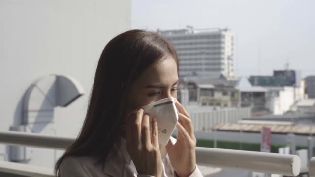 asian woman are going to work.she wears n95 mask.prevent pm2.5 dust and smog - mask стоковые видео и кадры b-roll