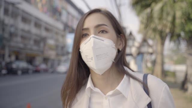 asyalı kadın çalışacak. n95 maskesi giyiyor. pm 2.5 toz ve smog önlemek. o öksürüyor - maske stok videoları ve detay görüntü çekimi