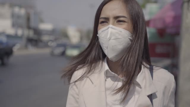 vídeos de stock e filmes b-roll de asian woman are going to work.she wears n95 mask.prevent pm2.5 dust and smog.she is coughing - cultura tailandesa