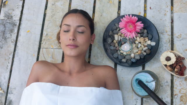 Asian woman at the spa Portrait of a beautiful Asian woman at the spa lying down with eyes closed spa treatment stock videos & royalty-free footage