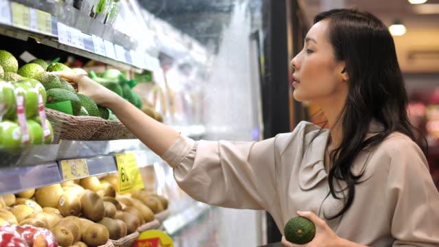 asiatische frau avocado obst einkaufen im supermarkt - supermarkt einkäufe stock-videos und b-roll-filmmaterial