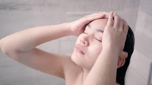 アジアの女性は入浴し、彼女の髪を洗います。 - 体 洗う点の映像素材/bロール