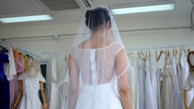 Asian woman, beautiful bride smiling happily at the dressing room Asian woman, beautiful bride smiling happily at the dressing room tulle netting stock videos & royalty-free footage