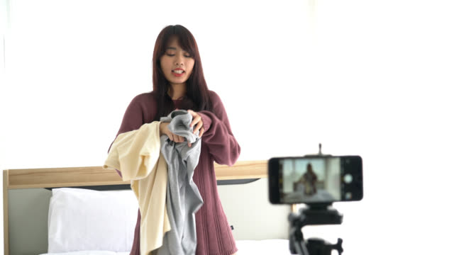 asian woman blogger showing clothes on camera to recording vlog video live streaming at her shop - vídeo
