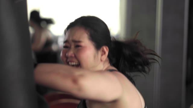 asian woman boxing punshing bag - sacco per il pugilato video stock e b–roll