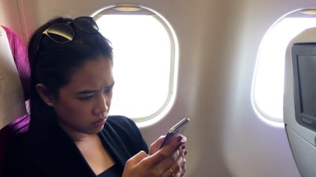 아시아 여자는 비행기에 스마트폰 검색 - airplane seat 스톡 비디오 및 b-롤 화면