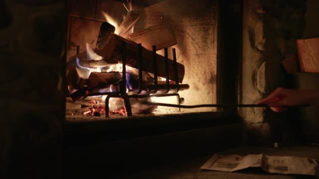 asyalı kadın bir kış köşkünde şömine günlükleri yanan - şömine odunu stok videoları ve detay görüntü çekimi