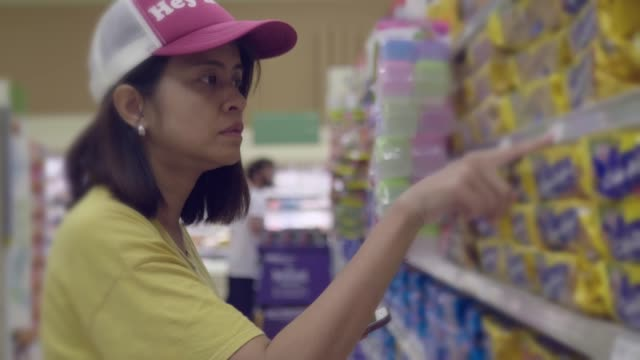 Asian woman buying food in supermarket Asian Hipster Woman shopping in Supermarket with Smart phone, Bangkok, Thailand. snack aisle stock videos & royalty-free footage