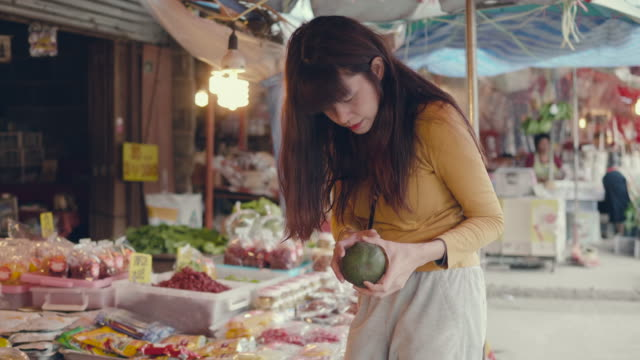 asian woman buying fruit and veg at a market - 30 34 anni video stock e b–roll