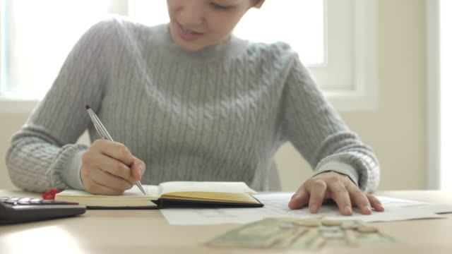 Asian Woman calculate about cost and doing Home Finances at Home