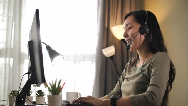 asian woman call support at home - słuchawki filmów i materiałów b-roll