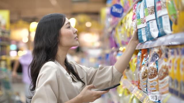asiatische frau checking auf smartphone, lebensmitteleinkauf im supermarkt - etikett stock-videos und b-roll-filmmaterial