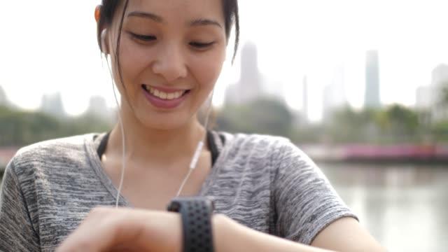 アジアの女性はスマートな時計のパルスをチェック ビデオ