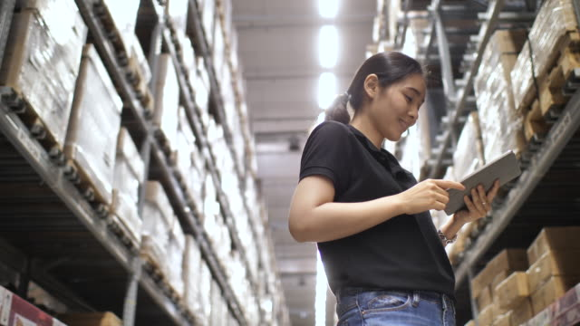 Asian Woman checking supplies on Digital tablet in the warehouse Asian Woman checking supplies on Digital tablet in the warehouse storage room stock videos & royalty-free footage