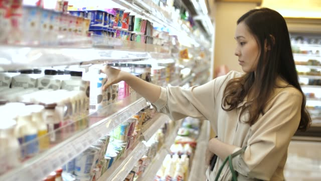 asian woman chooses milk in the supermarket - origini video stock e b–roll