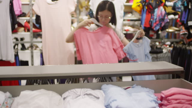 Asian Woman Choosing between Two Tops in Shop Dollying lockdown shot of Asian girl standing in clothing store, holding two casual blouses on hangers, putting them to her chest, choosing one, hanging another back on rack and walking away coathanger stock videos & royalty-free footage