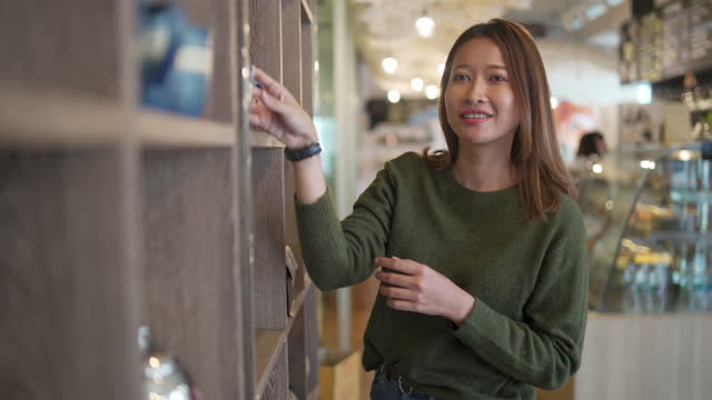 stockvideo's en b-roll-footage met aziatische vrouw die de apparatuur van het koffiebrouwsel in koffiewinkel bij winkelend winkelcentrum kiest - aziatische etniciteit