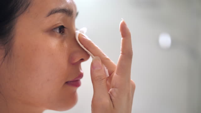 Asian Woman cleaning face in the bathroom at home
