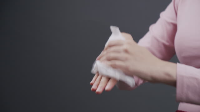 Asian woman cleaning her dirty hands with baby wipe paper. Adult woman using white wet tissue to cleanup her hand. healthcare,Hygiene and  beauty concept on gray background with copy space. close up