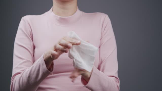亞洲婦女用嬰兒擦紙清潔她的髒手。成年婦女使用白色濕紙巾清理她的手。灰色背景上的醫療保健、衛生和美容概念,具有複製空間。特寫 - 濕的 個影片檔及 b 捲影像