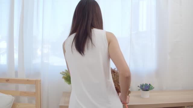 居間を掃除するアジア人女性、自宅の棚に羽毛掃除ダストを使った美しい日本人女性。時間クリーニングホームコンセプトを使用したライフスタイル女性。スローモーションショット。 - きれいにする点の映像素材/bロール
