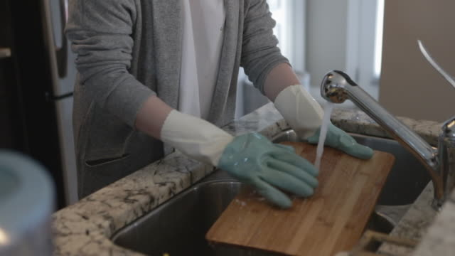 Video asian woman cleaning kitchen