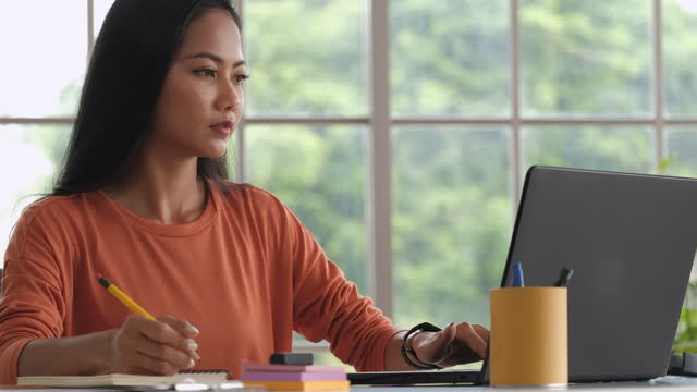 asian woman content creator writing  content on notebook and working from home.planning marketing, plan of project on planner