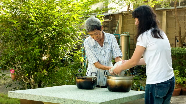 Asian woman cooking in the garden video