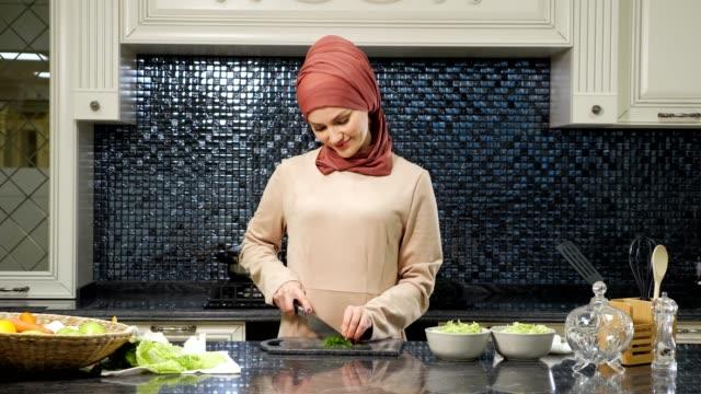 vidéos et rushes de la femme orientale cuisine le repas coupant les verts frais souriant - cuisine non professionnelle