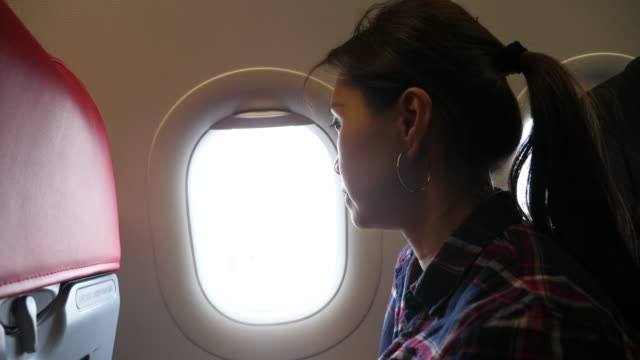 Asian woman coughing Asian woman coughing in the airplane. coughing stock videos & royalty-free footage