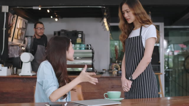 asian woman customer complaining to waitress about food in cafe restaurant, unhappy customer service in coffee shop