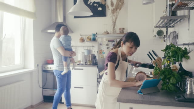 Asian woman cuts pork and uses digital tablet as a cookbook
