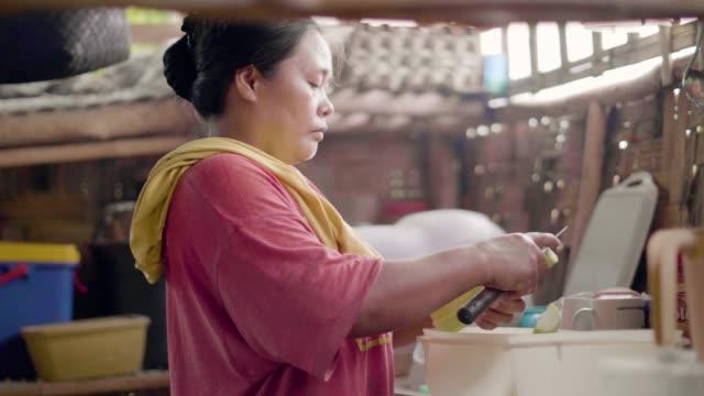 asiatische frau schneidet gemüse beim kochen von lebensmitteln in der hausküche. hausfrau kocht vegetarisches abendessen in traditioneller küche im bambushaus. häusliche asiatische küche. - stamm stock-videos und b-roll-filmmaterial