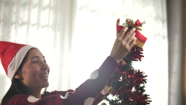 Asian Woman Decorating the christmas tree