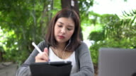istock Asian woman designer using digital pen to draw on graphic tablet and listening music relaxedly in park of university, pan shot 1165369966