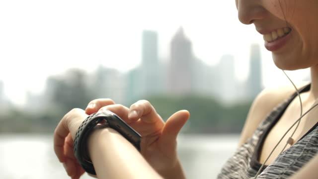 asian woman doing exercises with smartwatch - computer indossabile video stock e b–roll