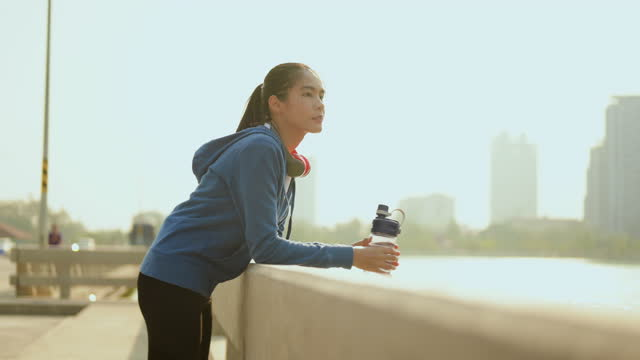 Asian woman drinking water and looking at city view after morning exercise on the bridge.Excercise,running,jogging, fitness and healthy lifestyle concept.