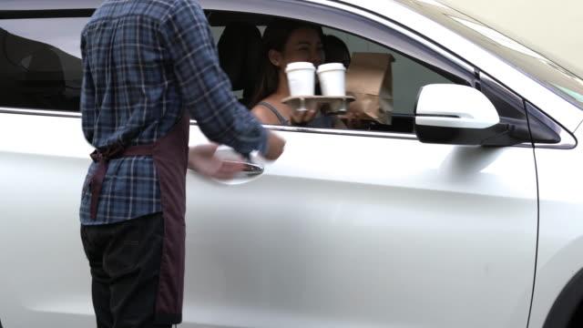 asiatische frau autoautofahrt und abholung von essen und kaffee von mitarbeiter über fahrt durch station des restaurants - schnellkost stock-videos und b-roll-filmmaterial