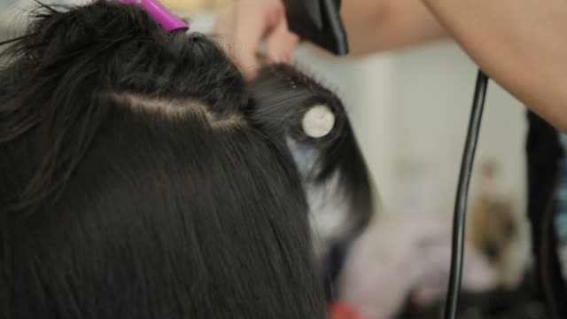 Asian woman drying hair after haircut in beauty salon video