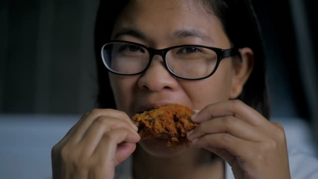 Asian woman eating fried chicken, Slow motion video