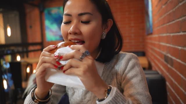 asian woman eating hamburger in fast food restaurant - węglowodan jedzenie filmów i materiałów b-roll