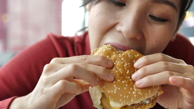 vídeos de stock e filmes b-roll de asian woman eating hamburger - hambúrguer comida