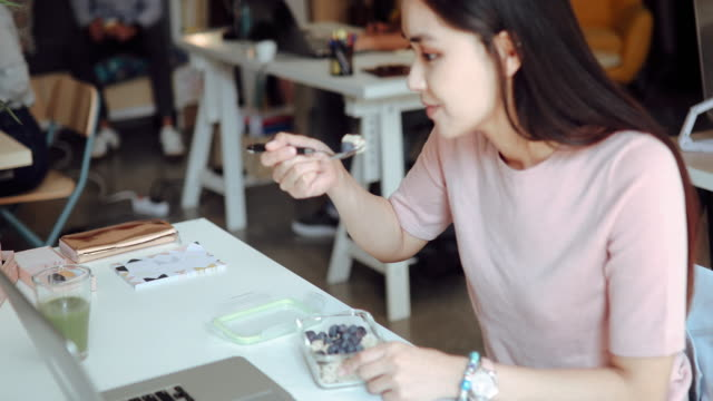 vídeos y material grabado en eventos de stock de mujer asiática comiendo desayuno saludable en la oficina - arándano