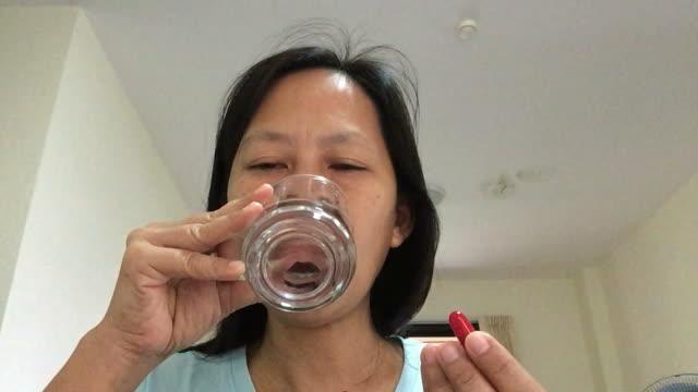 アジアの女性の食べる丸薬 - 抗生物質点の映像素材/bロール