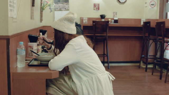 Asian woman eating ramen in restaurant.