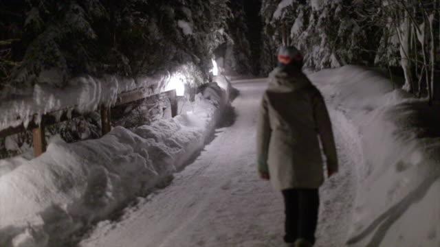 asian woman enjoy the snow at night