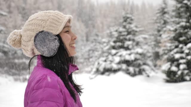 Asian Woman enjoying a snowy in winter forest