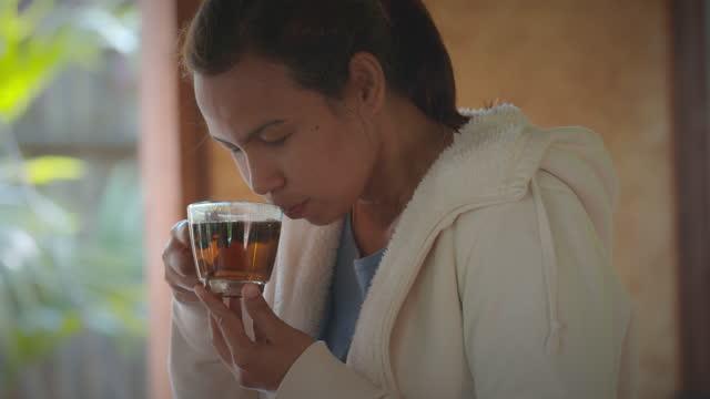 asyalı kadın zevk ve sabah saatlerinde mutfakta evde dinlenirken sıcak çay kokusu kokusu kokuyor. yavaş çekim. - nebat stok videoları ve detay görüntü çekimi