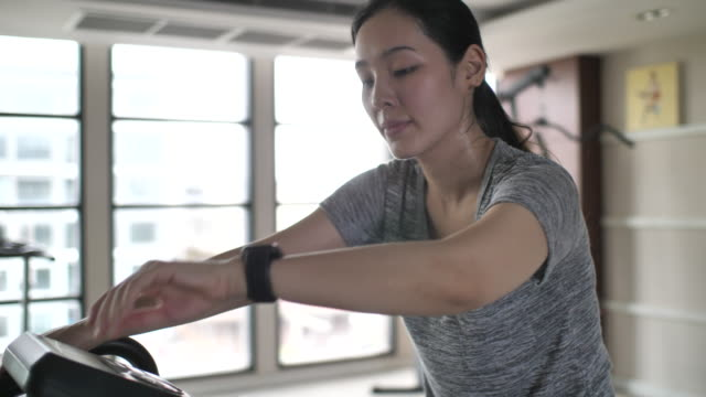 Asian Woman Exercise Cycling in Gym and using Smart watch for tracking plus Asian Woman Exercise Cycling in Gym and using Smart watch for tracking plus exercise bike stock videos & royalty-free footage