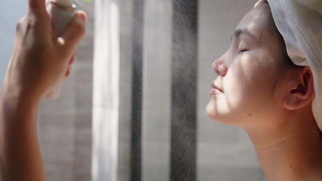 vídeos de stock e filmes b-roll de asian woman facial treatment with mineral water spray. - pulverizar